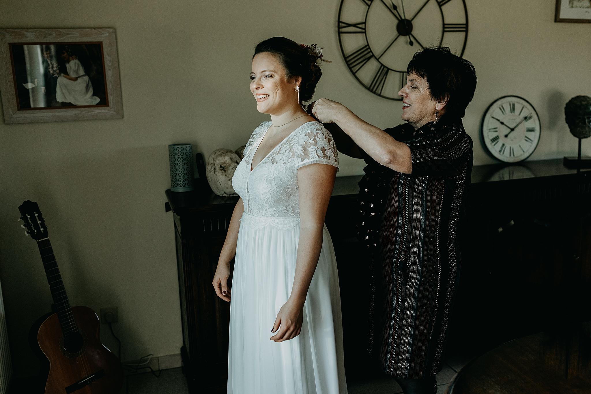 moeder helpt bruid juwelen aandoen