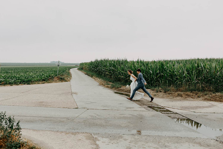 Bruidspaar springt over waterplas