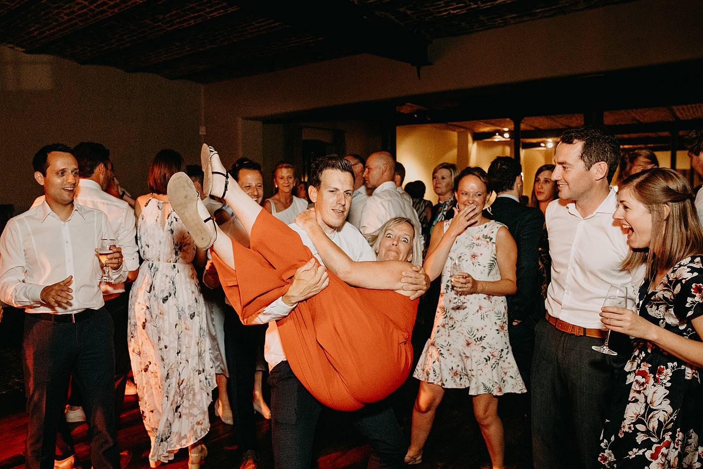 vriend draagt vriendin dansvloer huwelijk