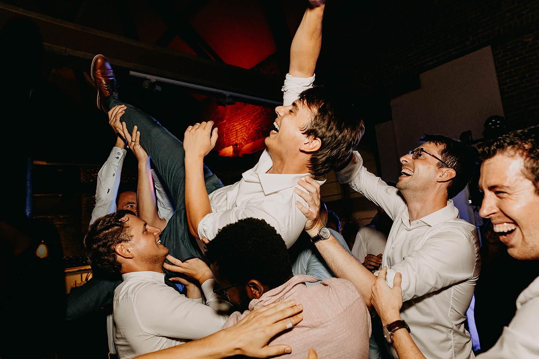 vrienden dragen bruidegom dansvloer