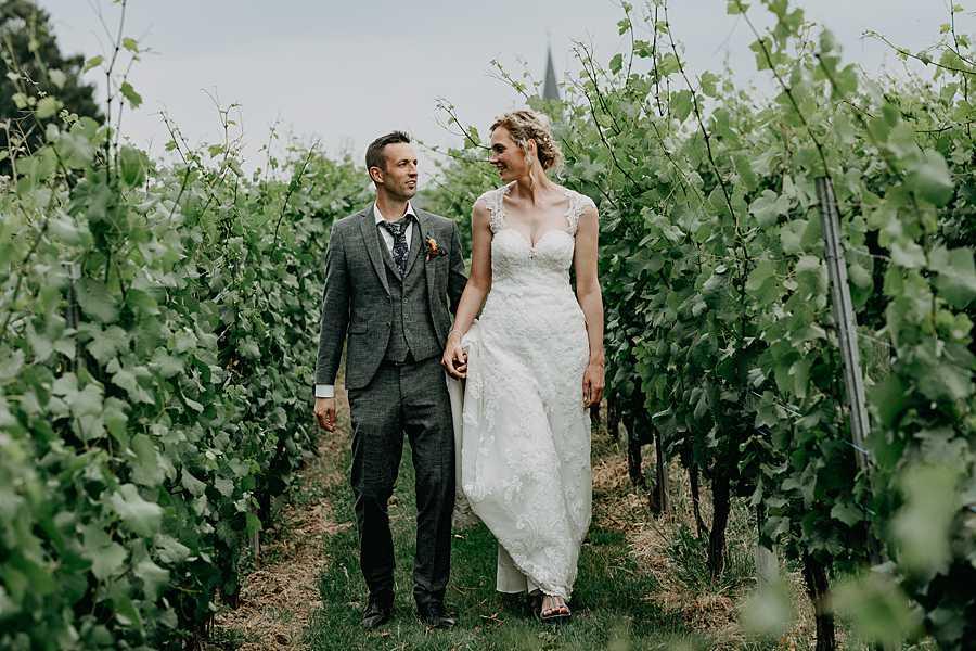 Wijnkasteel Genoelselderen bruidspaar wandelt tussen wijngaarden