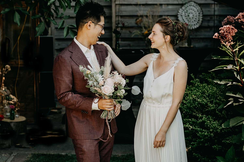 Bruid groet bruidegom bij first look in tuin