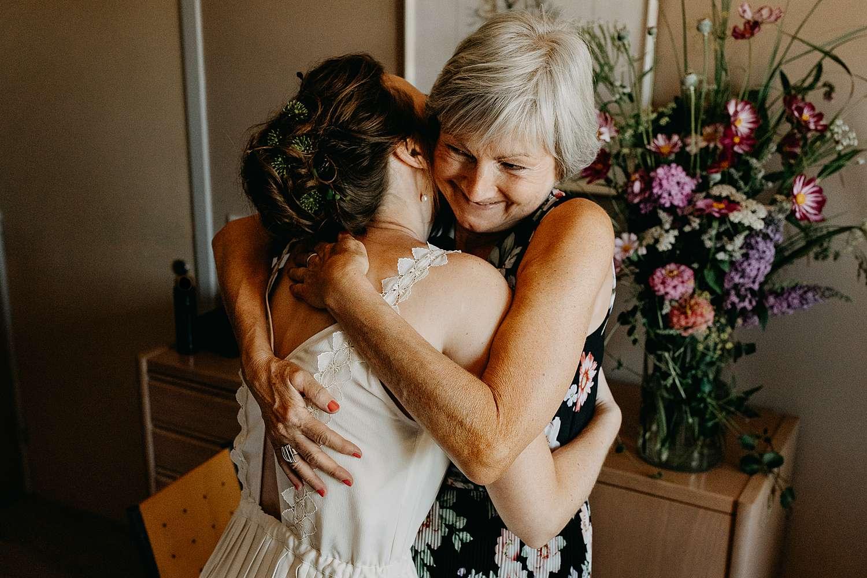 moeder knuffelt bruid bij voorbereiding