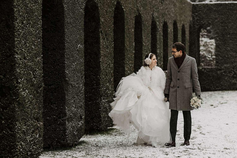 Bruidspaar wandelt tuin in sneeuw Kasteel van Hulpe