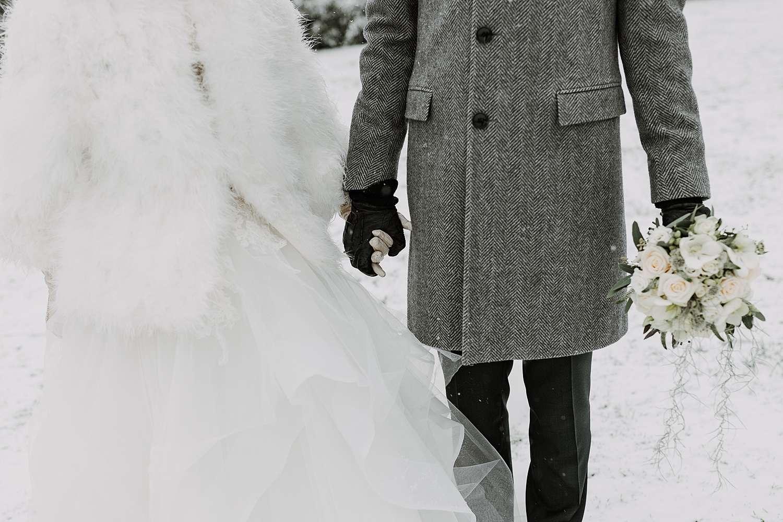 Handen vasthouden bruidspaar sneeuw