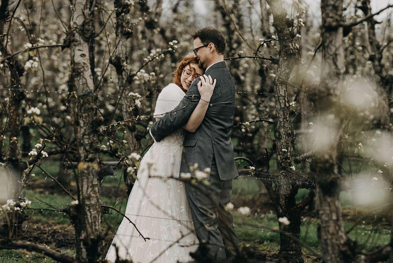 Bruidspaar knuffelt tussen bloesems