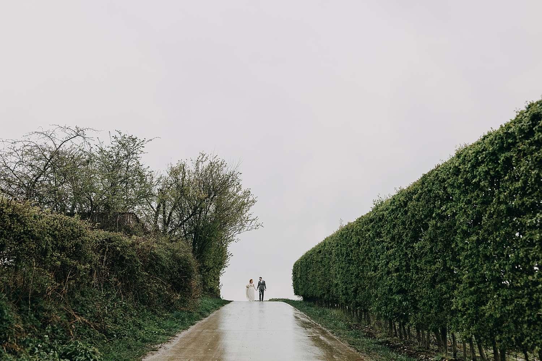 Bruidspaar wandelt naar doorkijkkerkje in regen Borgloon