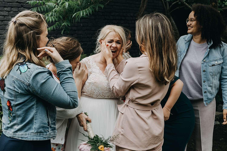 Bruid lacht na groepsfoto huwelijk