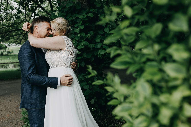 Bruidspaar knuffelt in park van Lier
