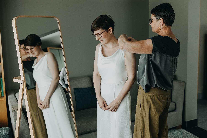 Aankleden bruid moeder knoopt bruidsjurk