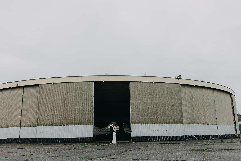 Bruidspaar in opening poort loods vliegveld Grimbergen