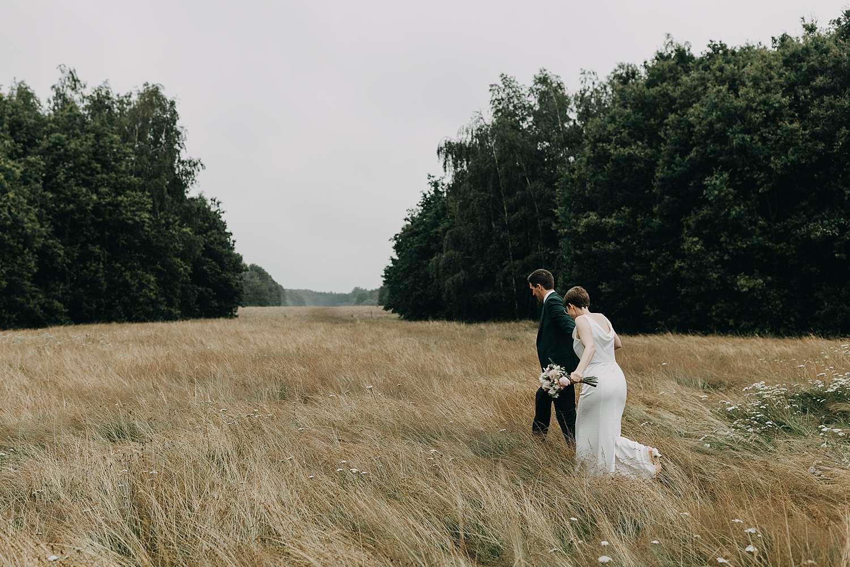 Bruidspaar wandelt door hoog grasveld Grimbergen