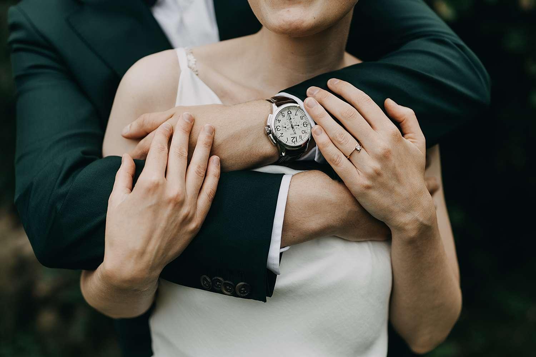 Detail armen knuffel bruidspaar