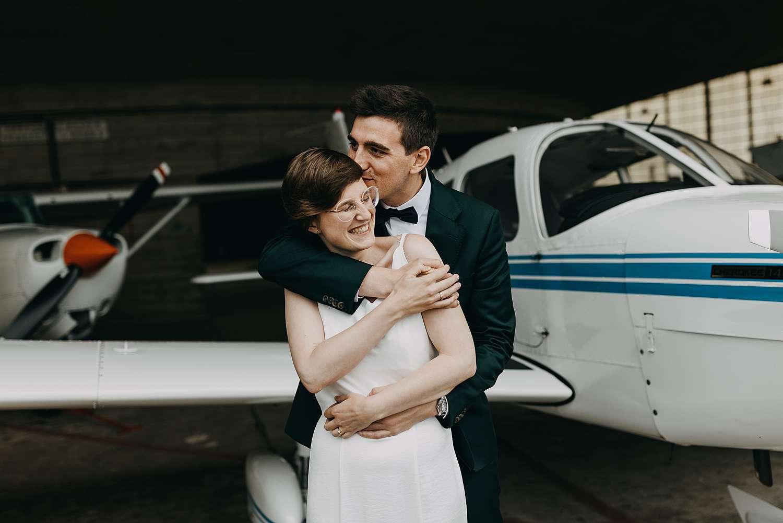 Knuffel bruidspaar huwelijk loods vliegveld Grimbergen